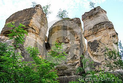 Giant sand-stone pillars in the geological parc of Gradina Zmeilor, Romania. Three standing cliffs with vegetation around them.