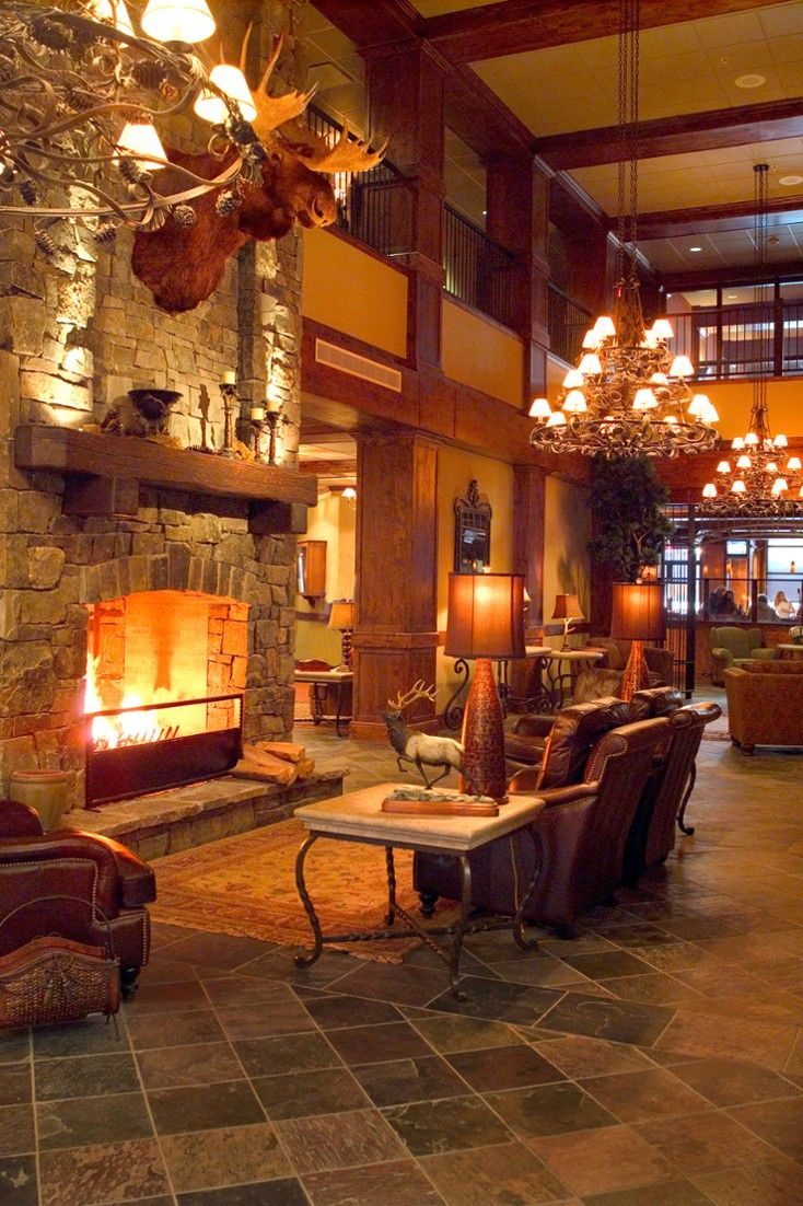 Lodge at Whitefish Lake Montana - The lobby has rustic cabin decor, with a stone fireplace, dark wood and leather chairs. #Jetsetter