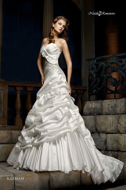 Женственное свадебное платье из сияющей атласной ткани, украшенное объемными складками.