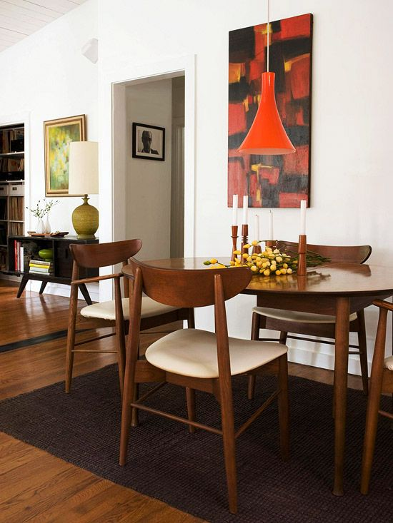 The dining area is simple yet elegant with its unique table and chair set. The orange abstract painting by Robert Irwin hanging above the table adds color and interest to the white walls. Plus, it's a great conversation starter.