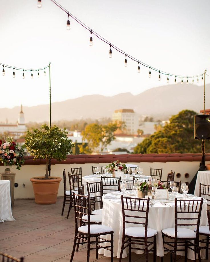 Rooftop Wedding Reception in Sunny Santa Barbara, CA at Canary Hotel: Decor features white and earthy tones, with vintage string lights.