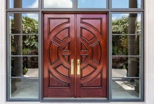 Asian-themed front door with exterior stone floors, transom window, double carved wooden doors. Elegant and serene.
