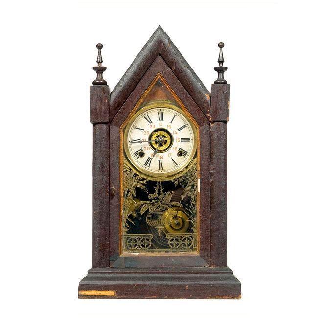 RELOJ CAPILLA AMERICANO Reloj de sobremesa,C. 1900. Waterbury clock company (USA). Caja en madera ebonizada y dorada. Esfera blanca con numeración romana en negro y agujas tipo pera. Medidas: 44 x 29 x 12 cm.