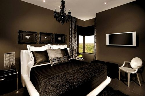 Dark bedroom, really like the dark wall, frames and crystal.