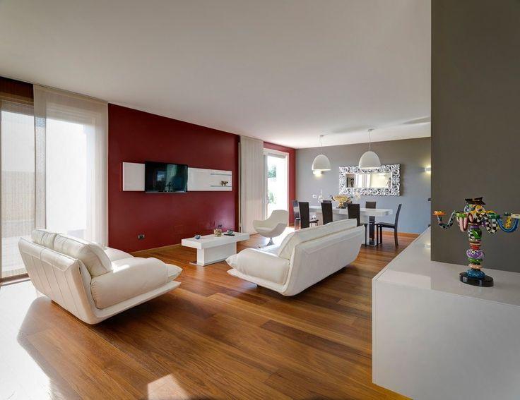 Soggiorno contemporaneo moderno con pareti rosso porpora e grigio tortora. Divani bianchi e pavimenti in legno