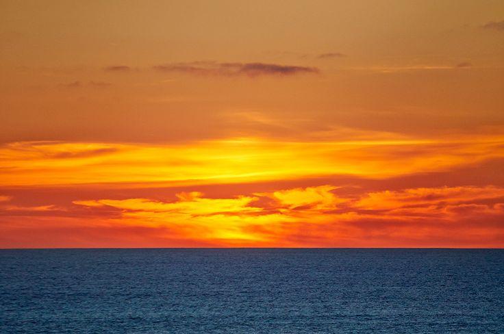 Fiery sunset off the coast of Muriwai, New Zealand.