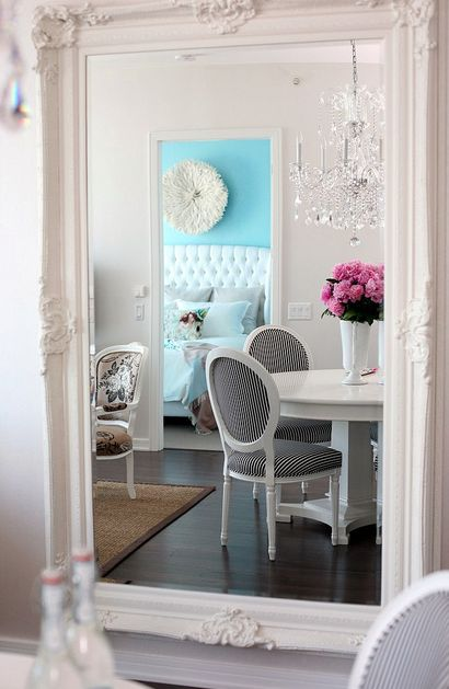 The Cross Design & Decor- chic, sophisticated french dining room design w/ white ornate baroque floor mirror, white round pedestal table, upholstered Louis chairs, sisal rug and crystal chandelier.