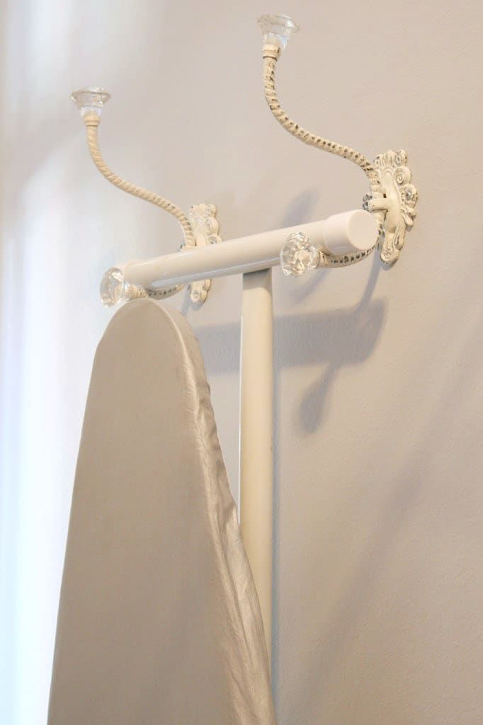 Find two sturdy hooks that are your style, and hang them near each other (measure the length of your ironing board's foot, so you know what distance will work). From here.