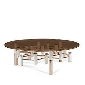 Konstantin is a low center table produced with a distinctive brown smoked glass top and a brass trim. It features an elaborated central structure made of tubes, some finished in glossy white, others with a mix of polished brass.