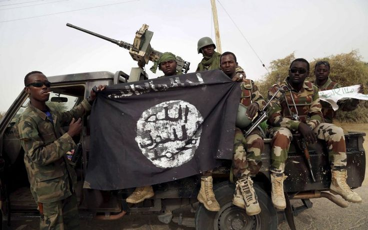 Nigerian soldiers hold up a Boko Haram flag that they had seized in the recently retaken town of Damasak, Nigeria, March 18, 2015. Chadian and Nigerien soldiers took the town from Boko Haram militants earlier this week. The Nigerian army said on Tuesday it had repelled Boko Haram from all but three local government districts in the northeast, claiming victory for its offensive against the Islamist insurgents less than two weeks before a presidential election. Picture taken March 18…