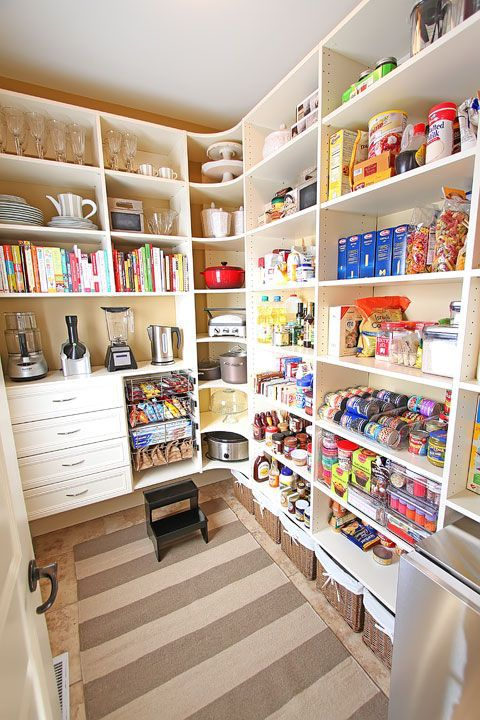 Never underestimate the power (and glamour) of built-in shelving. Here, floor-to-ceiling organizers provide plenty of space for food, allowing the back wall to be dedicated to prized possessions like heavy-duty appliances and breakable china. See more at Kevin and Amanda » - HouseBeautiful.com