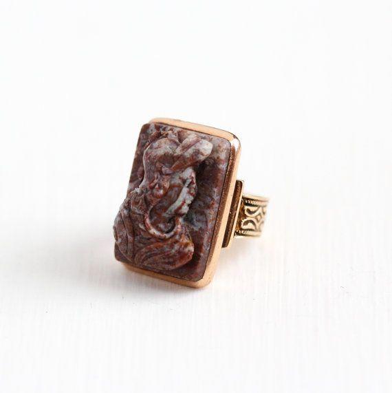 Impresionante antiguo 10k época victoriana oro rosa cameo el anillo. El anillo contiene un hermoso tallado piedra dura de multi color con colores púrpuras / marrón acentuados con blanco. La configuración contiene diseños decorativos de hombro desplazamiento. Hermosa pieza de joyería antigua fina! * Venta - precio reducido de $250 a $195.  ÉPOCA - fines del 1800, época victoriana  METAL / MATERIAL - 10 k color de rosa, oro, piedra dura  SEÑAS DE IDENTIDAD / HISTORIA - N/A  CONDICIONES - buen…