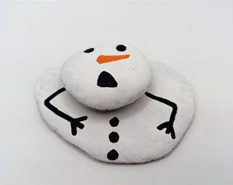 melting snowman beach pebbles