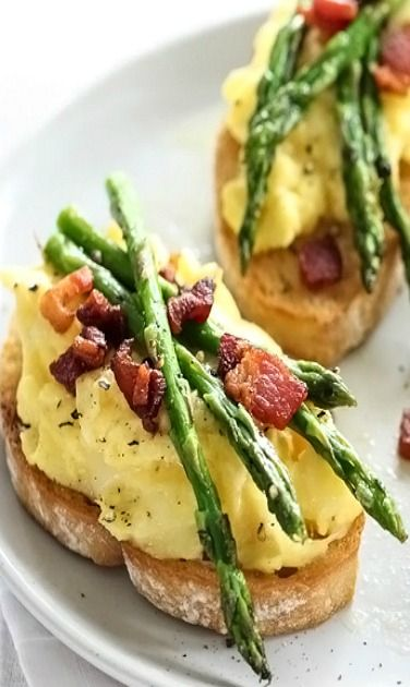 A delightful combination of sour dough toast covered with scrambled eggs, bacon and tiny asparagus spears.