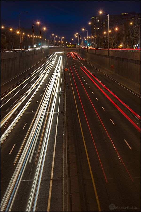 This is a long exposure photograph of the Decarie Expressway in Montreal taken during the blue hour. The Decarie expressway is a highway that runs North/South in Montreal, Quebec, Canada
