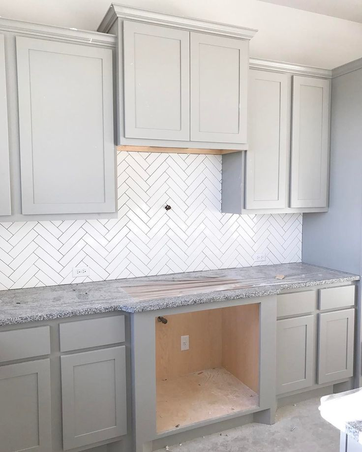Progress Pic! Backsplash is in! No grout yet (Mapei Warm Gray coming in) but we are loving the 2x8 tiles and herringbone pattern. #ourfauxfarmhouse2.0 is coming, y'all. Closing 3/31 . First project-removing builder grade granite and replacing with a custom slab we found . Can't wait to show you! #somanyprojectslinedup