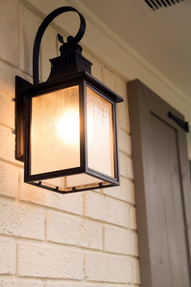 HGTV: The front entrance of the Gulley home is illuminated by a modern outdoor sconce.