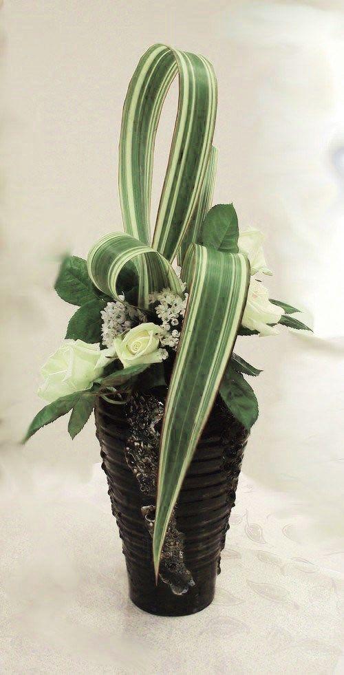 Vase peint en noir avec de la Peinture céramique à froid.Composition : Du phormium posé en ruban et des roses blanches du jardin.