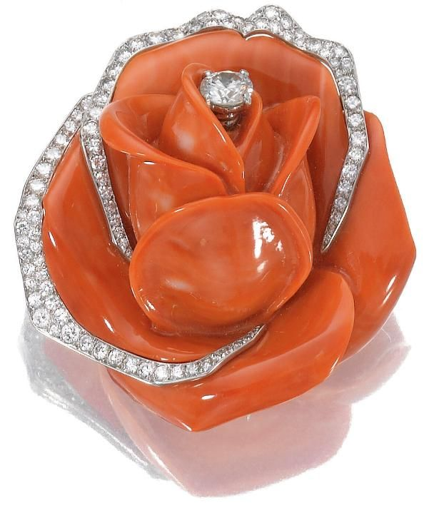 Coral and diamond brooch, Cartier, circa 1960. Designed as a carved coral rose, the centre and edges of the petals highlighted with circular- and single-cut diamonds, mounted in platinum and gold, signed Cartier Paris and numbered, French assay and maker's marks, accompanied by fitted case. Sotheby's.