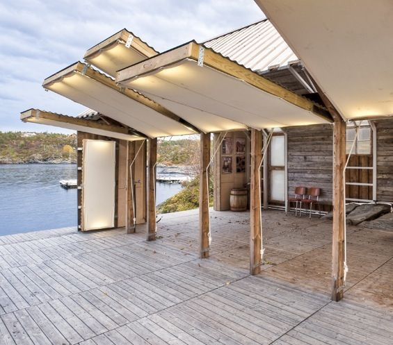 Norway. Small house of wood in s'inspirant traditional sheds to boats of the region with their rectangular plan and their big giving door on l'eau. Climbed on a structure of beams d'acier fixed to the rock, the small construction both contemporary and traditional s'ouvre on l'extérieur thanks to movable frameworks dressed alveolar polycarbonate and of canvas