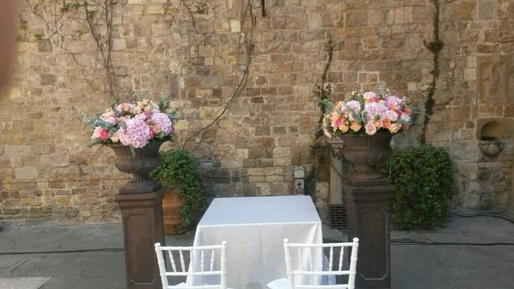 wedding ceremony decor with wide urns of coral pink flowers