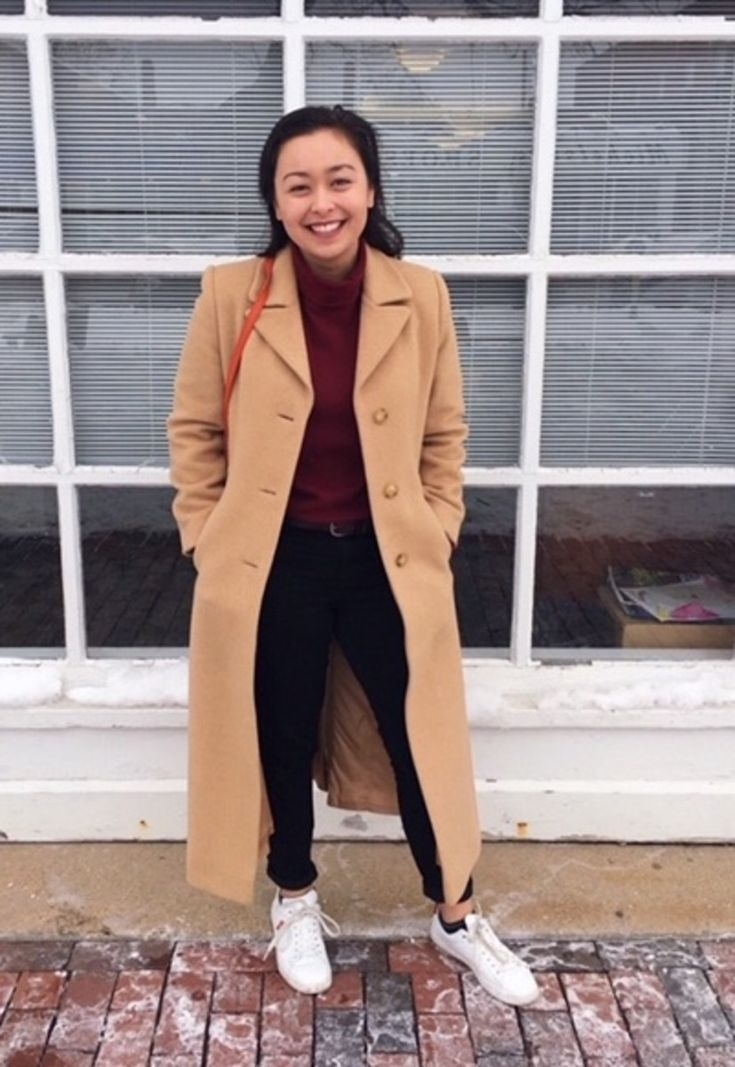 Suffolk University student Shannon looks stylish in the cold. She wears an ankle-length tan peacoat over a maroon turtleneck with belted black jeans and white sneakers.