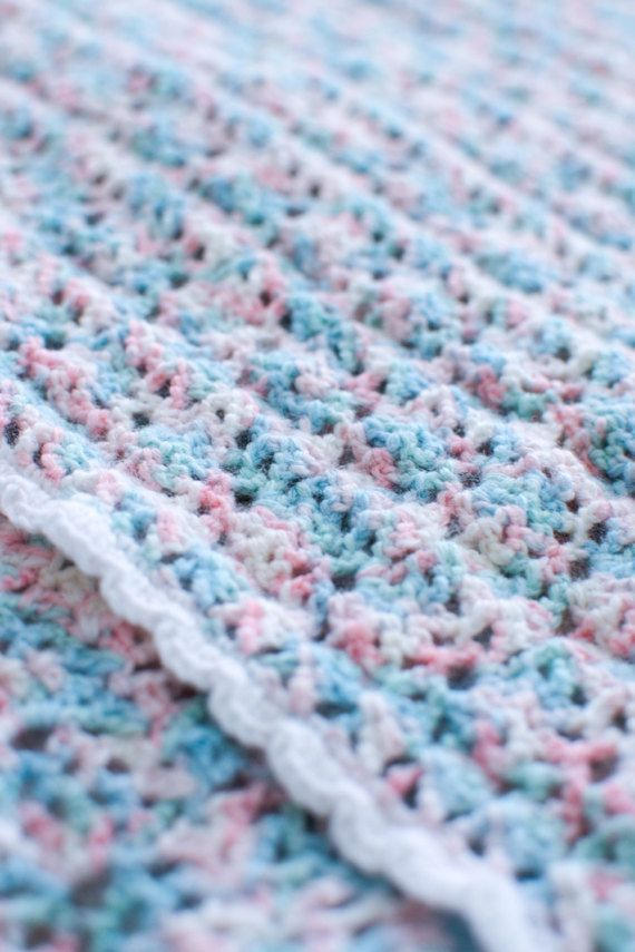 Lovely multicoloured crochet baby receiving blanket, made into a delicate but tight lace pattern and edged with a dainty white scallop pattern.  Hand made in Australia over the course of several weeks, this darling little blanket is ideal for baby shower gifts, for wrapping your little on up for snuggles, use in the pram or car seat, and is strong enough to last years of love. Made with 100% acrylic yarn, this blanket can be machine washed on a cold gentle cycle, and dried flat or folded in…