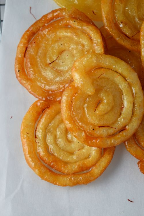 Crispy and sweet saffron syrup filled Indian funnel cake (Jalebis). Learn how to make these in very easy steps!NaiveCookCooks.com