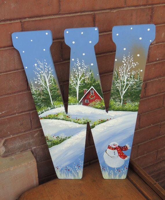 W is for Winter is a hand painted wooden letter W. It has a whimsical winter scene with a snowman in the forefront. Three dimensional snow
