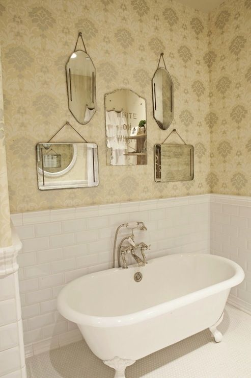 Sweet vintage bathroom with Thibaut Wallpaper, beveled subway tiles backsplash, claw foot tub, vintage penny tiles and collection of mirrors.