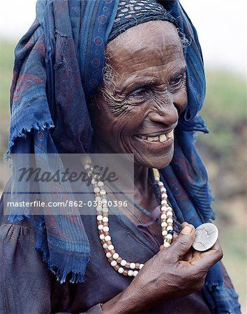 An Oromo old woman wears a necklace and a pendant made from a Maria Theresa thaler, an old silver coin minted in Austria, which was widely used as currency in northern Ethiopia and Arabia until the end of World War II. She was on her way to Senbete, an important weekly market close to the western scarp of the Abyssinian Rift.Afar nomads from the low lying arid regions of Eastern Ethiopia trek long