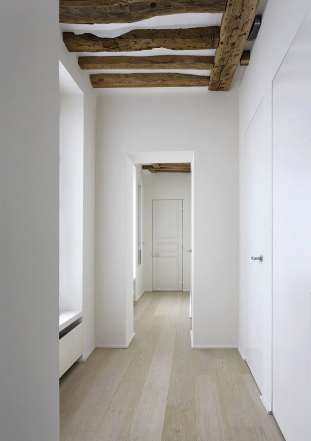 Brushed oak floors contrast with the exposed original ceiling beams.