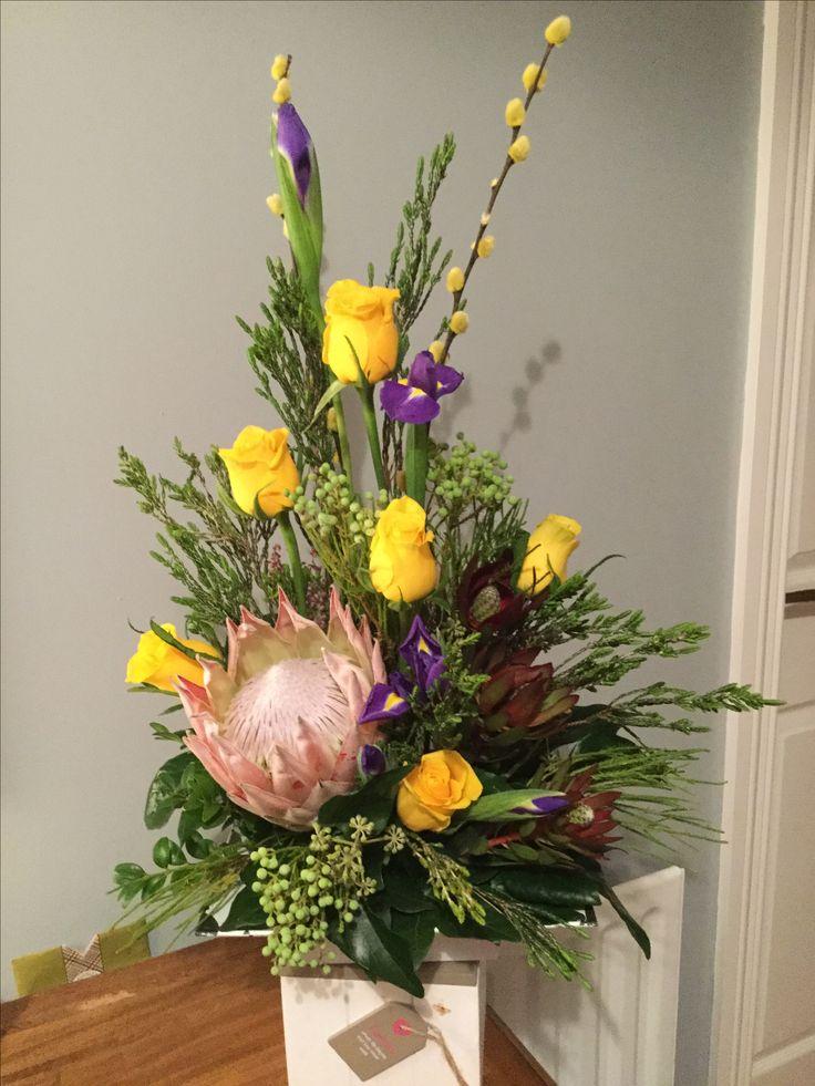 Protea, yellow roses and iris