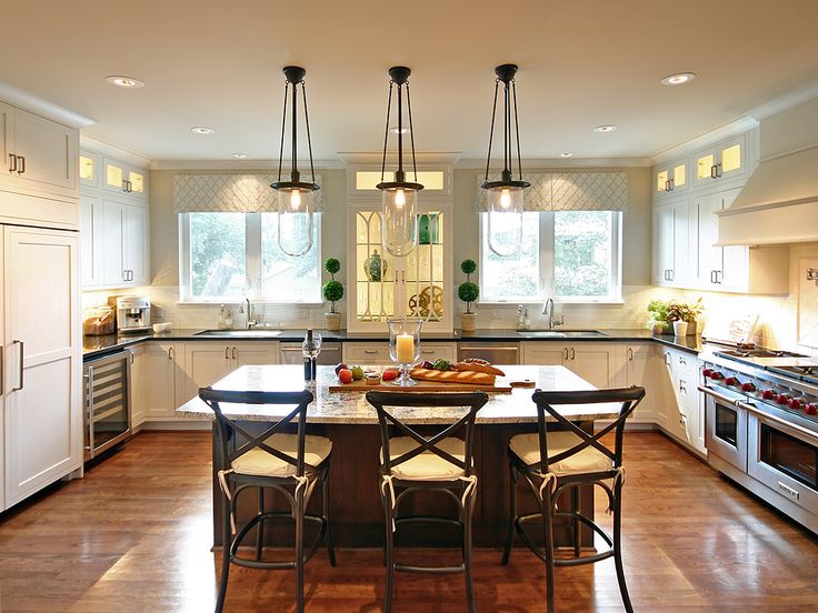 As we were after a transitional style that felt balanced and classic in nature, we arranged the space symmetrically down the center axis; the Sub-Zero refrigerator on one side and the Wolf range on the other. The kitchen features two windows, two sinks, two dishwashers, and a charming glass cabinet in the center for the storage of china and stemware. Just imagine how easy cleanup will be after dinner parties and holiday gatherings! Design by Avondale Design Studio.