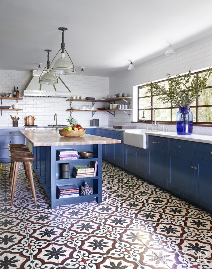 The kitchen features vintage pendants from Obsolete, BassamFellows stools from Design Within Reach, and a sink by Shaws with fittings by Jaclo. The custom-made cabinetry is painted in Farrow & Ball's Hague Blue, the countertops are Carrara marble, and the hood by Modern-Aire is custom made, as is the flooring by Granada Tile. - ELLEDecor.com
