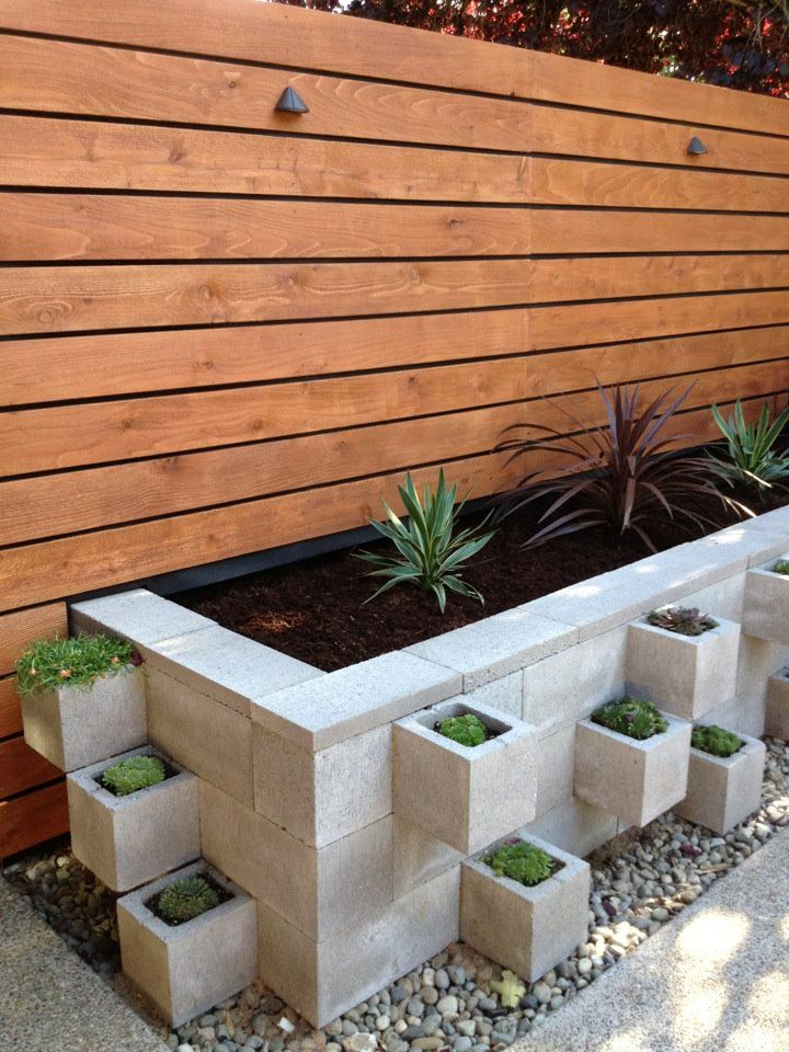Cinder blocks raised gardens. Top it off with those clover leaf screen blocks with moss growing in it for a softer look.