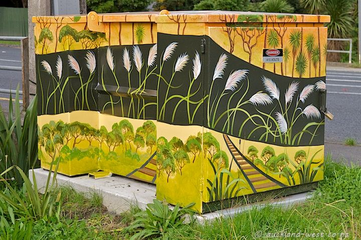 This transformer is in West Coast Road, Glen Eden, below the Waikumete Cemetery and near the Waikumete stream. It captures the essential elements of the location: manuka/kanuka shrubbery, the railway line, and most conspicuously the feathery heads of the toi toi on the hillside. The painter is Monique Endt.