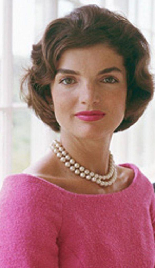Jacqueline Kennedy Onassis, esposa do presidente dos Estados Unidos John F. Kennedy. Podemos ver o seu penteado moderno e um dos marcos do seu estilo, tal como o seu colar.