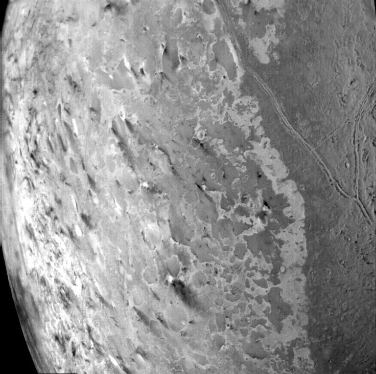 This image of the south polar terrain of Triton, (Neptune's Moon) taken on Aug. 25, 1989 reveals about 50 dark plumes or 'wind streaks' on the icy nitrogen surface.