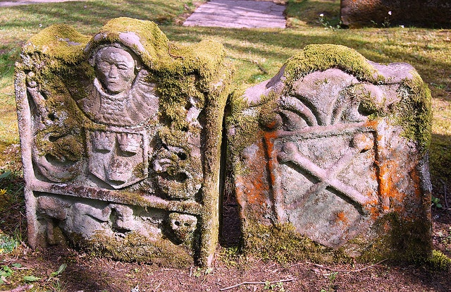 In the graveyard in Luss, on the banks of Loch Lomond, we found stones  dating back a millennium. Near one entrance was a Dark Age hogback  slab (not very photogenic), while this pair of moss-covered, chunky  gravestones leant on each other to survive the centuries.