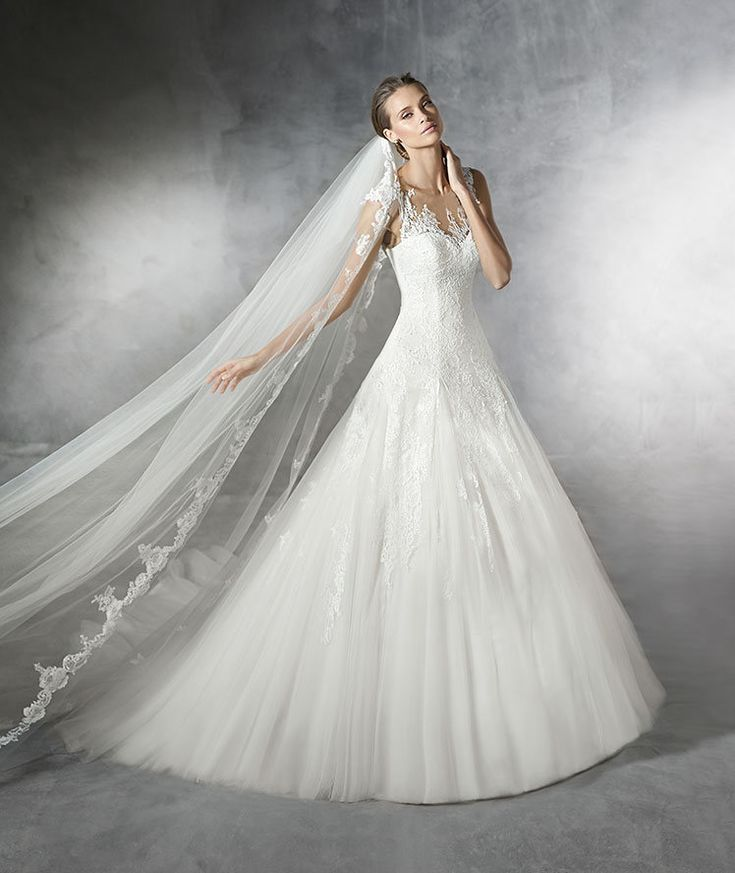 Tulle, A-line wedding dress with lace appliqués. Bodice with sweetheart neckline, sheer underbodice with lace appliqués front and back. Wide tulle skirt with godets.