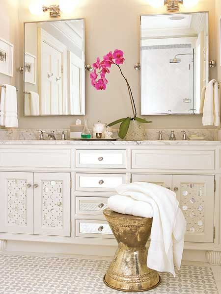 In this all-white bathroom, the small, glued-on mirrors add drama to ordinary cabinet doors. Don't forget to accessorize your bathroom as you would a living room -- plants are a great way to bring in interest and seasonal color. (Photo: Dominique Vorillon)