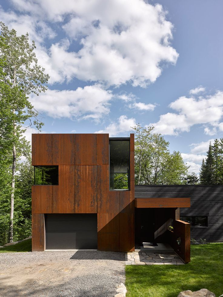 montreal architect paul bernier has completed a home clad in blackened timber and weathering steel on the shores of a lake in rural quebec