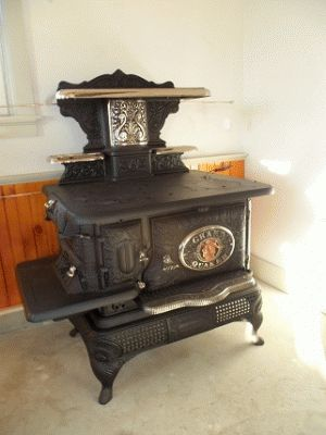 This a Grand Quaker from Taunton Iron Works, wood only stove. It was made around 1890 or so and was the most elaborate stove made by the company. It has all the filigree one would expect from a Victorian stove plus a Pie Puller to bring food to the front of the oven, and three drying racks that hide inside the high back when not in use. Also, all of the handles are people's faces.