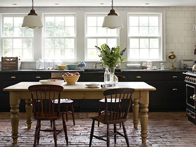 A local carpenter constructed the cabinets in this kitchen, painted black to match the range and topped with soapstone counters, in this New York farmhouse. The floor—made of bricks from the old chimney—is heated radiantly. The cabinets are painted Black Blue by Farrow  Ball.