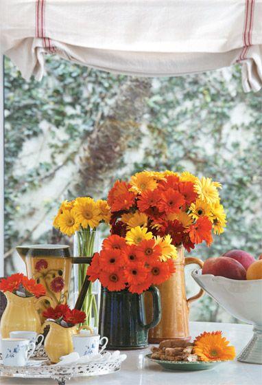 """Jarras viram vasos para minigérberas na proposta da florista Rebeca Kocubej. """"Além de fáceis de encontrar, as gérberas têm cores alegres e a cara de verão"""", diz Rebeca, que escolheu versões de vermelho, laranja e amarelo da flor. """"Para ficar equilibrado, procurei setorizar os tons. Só o vaso maior mistura todos."""":"""