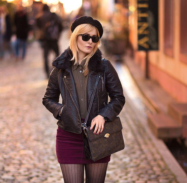 Christina Key trägt eine transparente Strumpfhose, einen Minirock in weinrot und eine schwarze Lederjacke mit Kunstfell