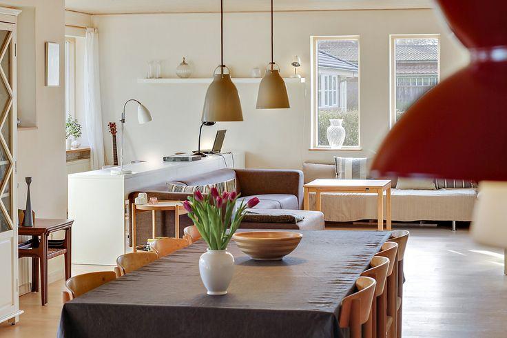 Stor spisestue og stue med vedligeholdelsesfri Velfac-vinduer i hvid alu udvendigt og lyst træ indvendigt. Trægulv i ask og lyst listeloft.