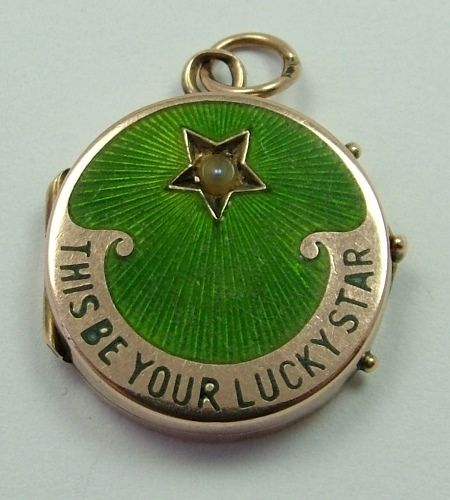 An Edwardian c1905 9ct rose gold and enamel 'This Be Your Lucky Star' locket charm with seed pearl to the front and two photo compartments inside.