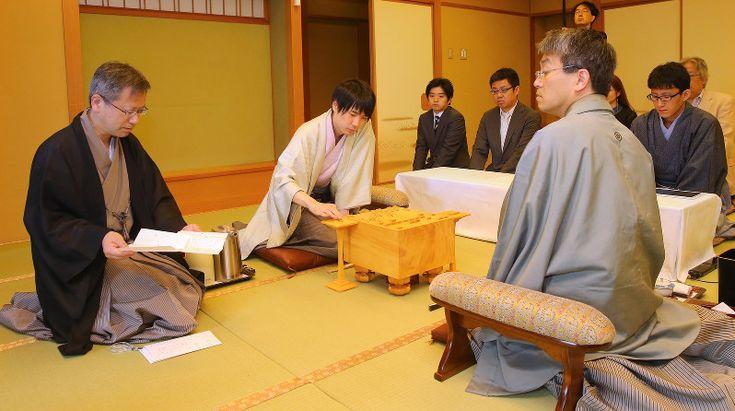 立会の中村修九段(左)から差し出された封じ手を見る羽生善治名人(手前右)。中央は佐藤天彦八段